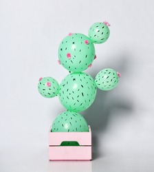 Cactus balloon in pastel pink flower pot made of green round balloons with flowers. Creative idea minimal concept on gray background