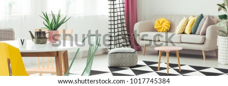 Cactus in pink pot and kettle on white round table in warm living room interior with yellow cushions on sofa, wooden stool and pouf on the carpet #1017745384