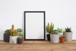 Cactus with black frame poster on table in room.trendy home decoration