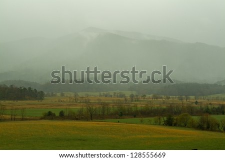 Cades Cove Valley Floor and mountains covered by clouds during rainstorm - stock photo