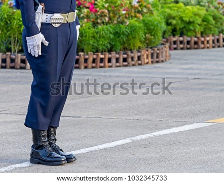 Cadet in Military dress uniform stand on the street.