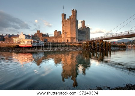 Caernarfon  castle, at sunset with its fortress towers and stronghold, overlooking the river Seiont at low tide