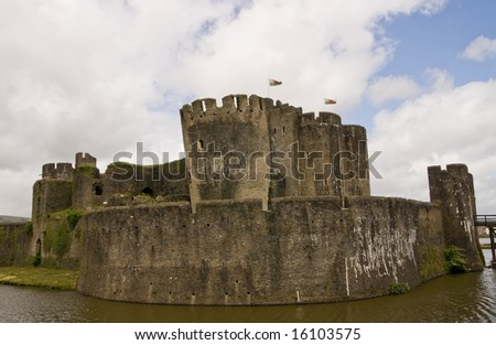Caerphilly Castle with Welsh flags in South Wales, UK - stock photo