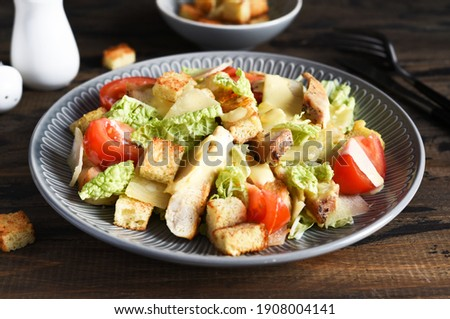 Caesaor salad. Salad with romaine leaves, chicken and tomans in a plate. Horizontal focus. Imagine de stoc ©