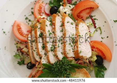 Caesar salad made of grilled chicken fillet garnished with parmesan