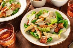 Caesar salad with a wine glass on a dark rustic wooden background