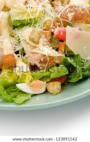 Caesar Salad with Grilled Chicken Breast, Garlic Crouton, Romaine Lettuce, Cherry Tomato, Eggs, Sauce and Grated Parmesan Cheese closeup on Green Plate