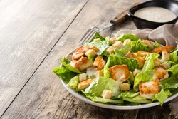 Caesar salad with lettuce,chicken and croutons on wooden table. Copyspace