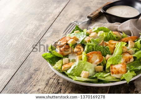 Caesar salad with lettuce,chicken and croutons on wooden table. Copyspace #1370169278