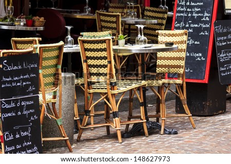Cafe at rue Mouffetard in Paris - traditional wicker furniture and menu boards exposed on the pavement, Paris, France