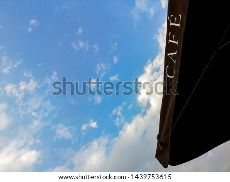 CAFE - cafe sign on a black umbrella against the blue sky and clouds #1439753615