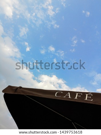 CAFE - cafe sign on a black umbrella against the blue sky and clouds #1439753618