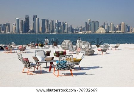 Cafe chairs with view of Doha downtown skyline, Qatar, Middle East