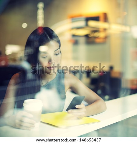 Cafe city lifestyle woman on phone drinking coffee texting text message on smartphone app sitting indoor in trendy urban cafe. Cool young modern mixed race Asian Caucasian female model in her 20s. #148653437