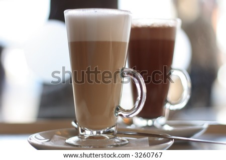 Cafe Coffee Latte in a glass with hot chocolate in background