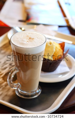 Cafe coffee - Latte in a glass with lemon muffin in background