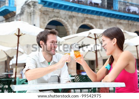 Cafe couple drinking talking having fun laughing smiling happy. Young interracial couple on travel vacation drinking rum in Old Havana, Cuba, Plaza de la Catedral.