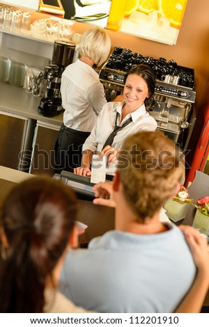 Cafe employee woman giving man bill receipt woman customer bar