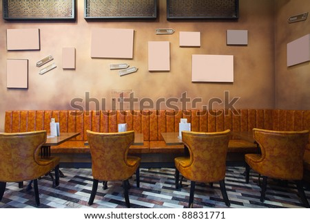 Cafe interior, vintage style, leather armchairs and empty frames on the wall.