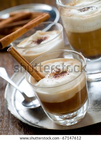 Cafe Latte in glasses with cinnamon stick  on plate