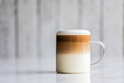 Cafe latte macchiato layered coffee in a see through glass coffee cup. The cup has a white wooden background.