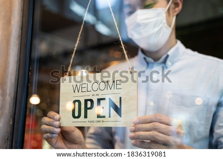 Cafe or restaurant and business reopen after Coronavirus quarantine is over. Man with face mask turning a sign from closed to open on a door shop. Small food shop business after post covid lockdown.