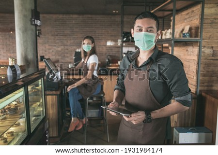 cafe owner wear face mask at his coffee shop using tablet pc. his partner sitting in a background. open for business in new normal protocol