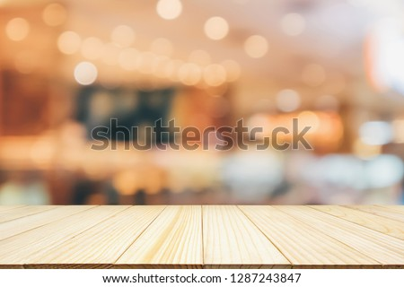Cafe Restaurant interior with customer and wood table blur abstract background with bokeh light for montage product display #1287243847
