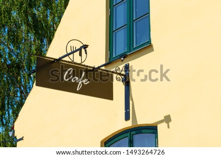 Cafe signboard on the background of the yellow wall. Close-up. Exterior. Decor.