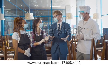 Cafe staff and manager on morning briefing wearing protective masks and gloves working during quarantine. Restaurant owner, waitresses and chef working during covid-19 pandemic