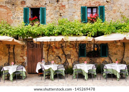 Cafe tables and chairs outside a quaint stone building in Tuscany, Italy #145269478