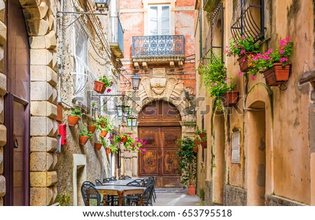 Cafe tables and chairs outside in old cozy street in the Positano town, Campania, Italy