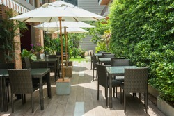 Cafe tables and chairs outside with big white umbrella and plant