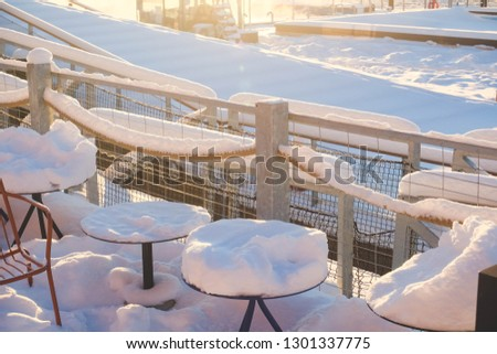 Cafe /terrace covered in snow on winter sunny day. Chairs snow covered case to harbor.