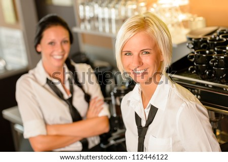 Cafe waitresses behind bar smiling at work break women colleagues - stock photo