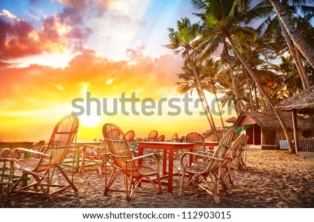 Cafe with beautiful view to the ocean on tropical coastline at sunset background in India
