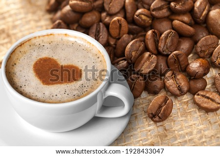Cafes and restaurants. A mug of black coffee with foam and coffee beans.