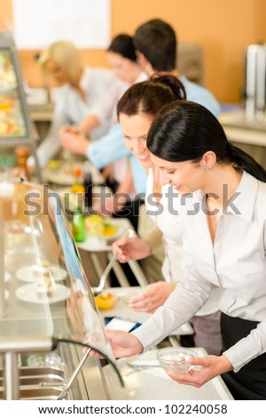 Cafeteria lunch two office colleagues woman choose food dessert self-service