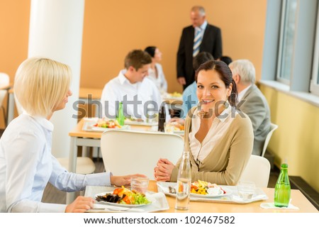 Cafeteria lunch young business women eat salad at office canteen
