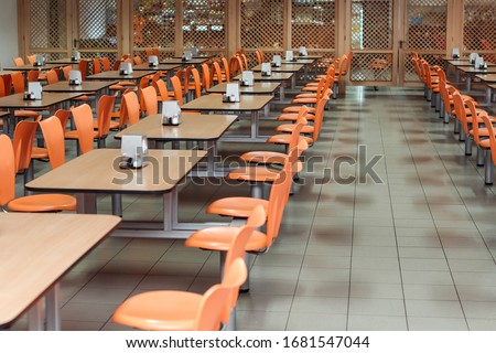 Cafeteria or canteen interior. School cafeteria. Factory canteen with chairs and tables, nobody. Modern cafeteria interior. Clean canteen in modern school. Lunch room.