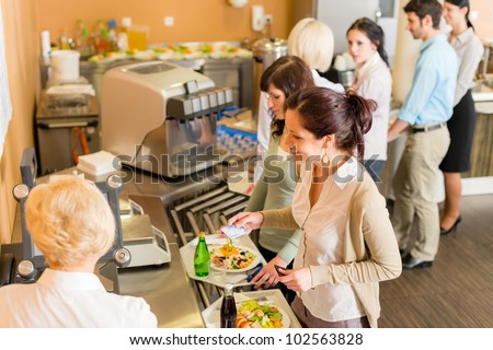 Cafeteria woman pay at cashier hold serving tray fresh food Stock photo ©