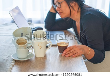 Caffeine addicted bad lifestyle concept. Young Asian woman holding a cup of coffee sitting tired with many empty cups of coffee and laptop on the desk. Focus on the hand and coffee. Сток-фото ©