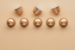 Caffeine, hot drinks and objects concept - close up of golden capsules or pods for coffee mashine on beige background. Top view with space for text. Flat lay..