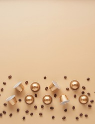Caffeine, hot drinks and objects concept - close up of golden capsules or pods for coffee mashine with some roasted grains on beige background. Top view with space for text. Flat lay..