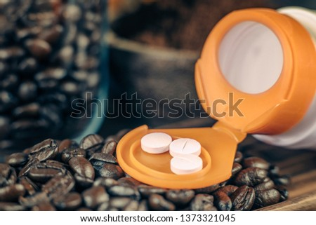 Caffeine supplementation bottle with pills and roasted coffee beans on a wooden plate