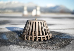 Caged roof drain with defocused vents and winter mountain background. Flat roof with exposed modified bitumen membrane. Inspect and clean roof drain system to prevent water damage. Selective focus.