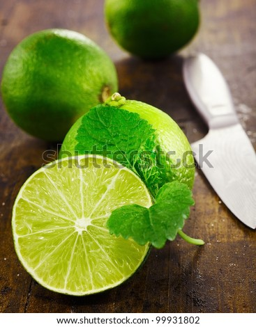 Caipirinha and Mojito accessories. Fresh limes with mint sliced with a knife on a wooden background