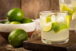 Caipirinha brasileira. Bebida de cachaça com limão, sobre fundo de madeira rústico.