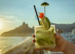 Caipirinha cocktail (with a kiwi twist) with Rio de Janeiro, Brazil beach background