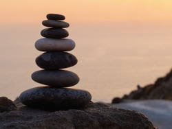 cairn at sunset, stones balances, pyramid of stones at sunset, concept of life balance, harmony and meditation